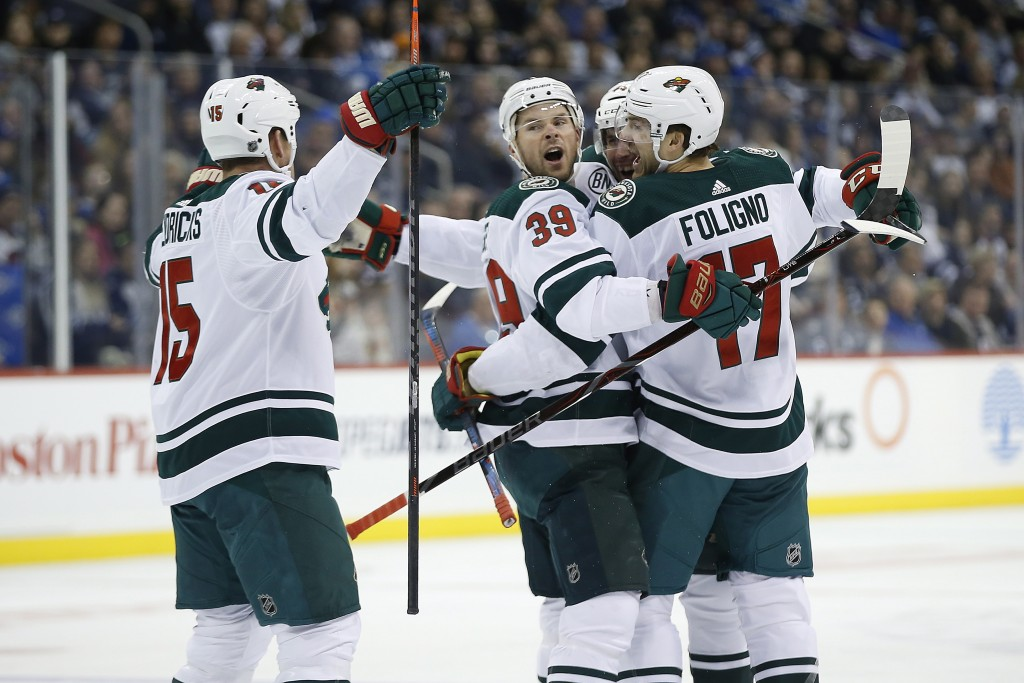 Minnesota Wild's Matt Hendricks (15), Nate Prosser (39), Matt Bartkowski (44) and Marcus Foligno (17) celebrate Bartkowski's goal against the Winnipeg...