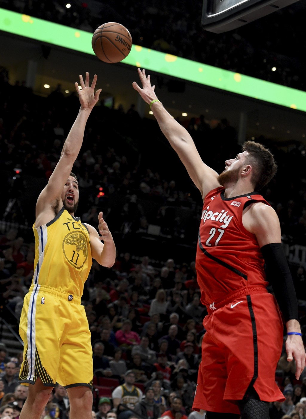 Golden State Warriors guard Klay Thompson, left, hits a shot over Portland Trail Blazers center Jusuf Nurkic, right, during the first half of an NBA b...