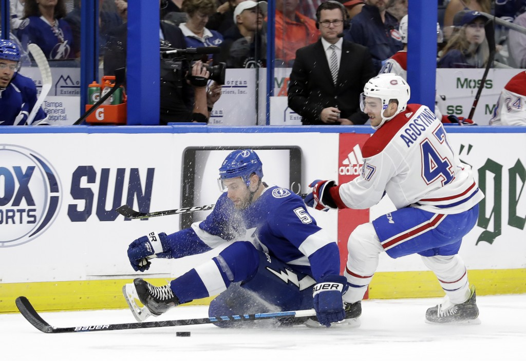 Montreal Canadiens left wing Kenny Agostino (47) takes down Tampa Bay Lightning defenseman Dan Girardi (5) as they chase the puck during the first per...