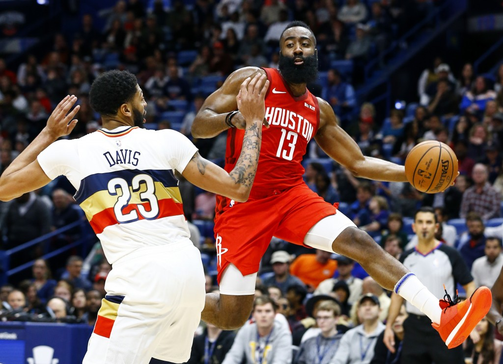 Houston Rockets guard James Harden (13) passes the ball around New Orleans Pelicans forward Anthony Davis (23) during the first half of an NBA basketb...