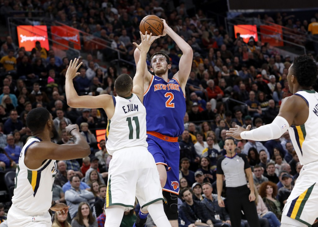 New York Knicks' Luke Kornet (2) shoots as he is defended by Utah Jazz's Dante Exum (11) in the first half of an NBA basketball game on Saturday, Dec....