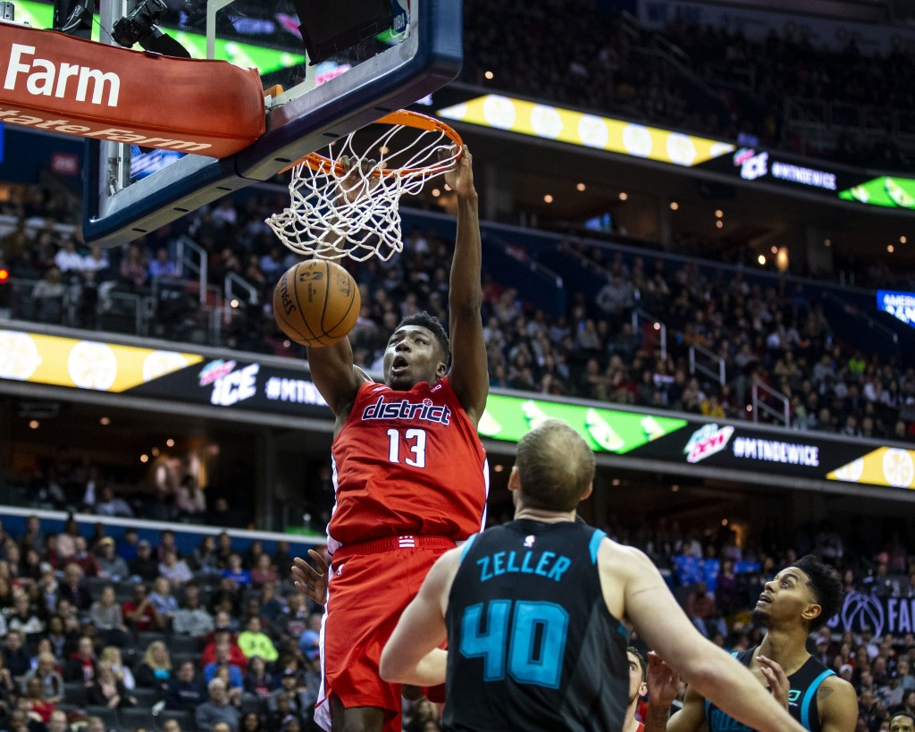 Washington Wizards center Thomas Bryant (13) dunks in front of Charlotte Hornets center Cody Zeller (40 during the second half of an NBA basketball ga...