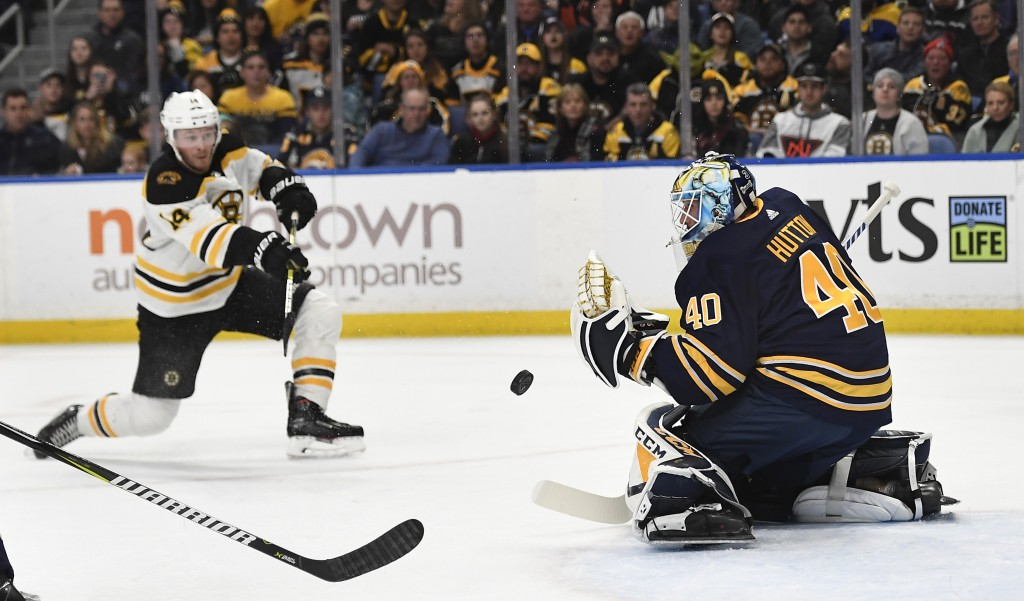 Buffalo Sabres goalie Carter Hutton (40) deflects a shot by Boston Bruins right wing Chris Wagner during the first period of an NHL hockey game in Buf...