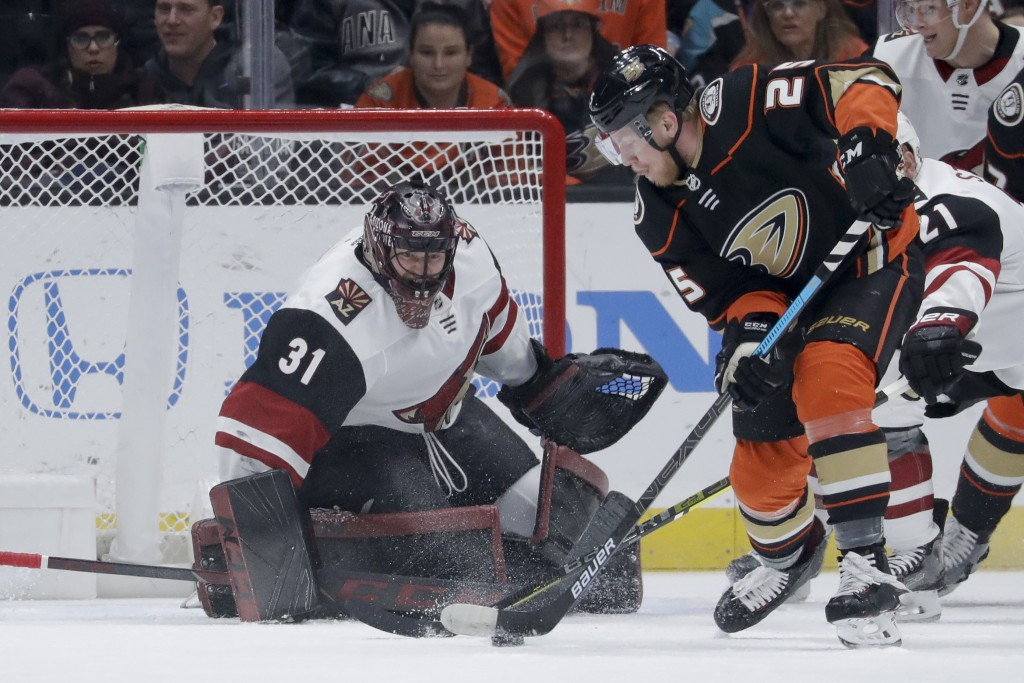 Arizona Coyotes goaltender Adin Hill, left, blocks a shot by Anaheim Ducks right wing Ondrej Kase during the first period of an NHL hockey game in Ana...