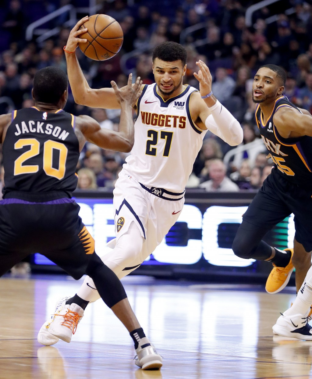 Denver Nuggets guard Jamal Murray (27) drives against Phoenix Suns forward Josh Jackson (20) during the first half of an NBA basketball game, Saturday...
