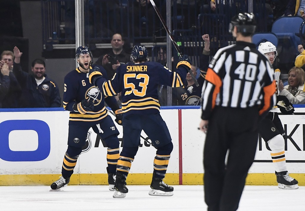 Buffalo Sabres defenseman Marco Scandella, left, celebrates his goal with left wing Jeff Skinner (53) during the first period of an NHL hockey game ag...
