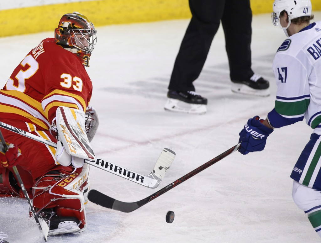 Calgary Flames goalie David Rittich, from the Czech Republic, makes a save as Vancouver Canucks' Sven Baertschi, from Switzerland, looks for a rebound...