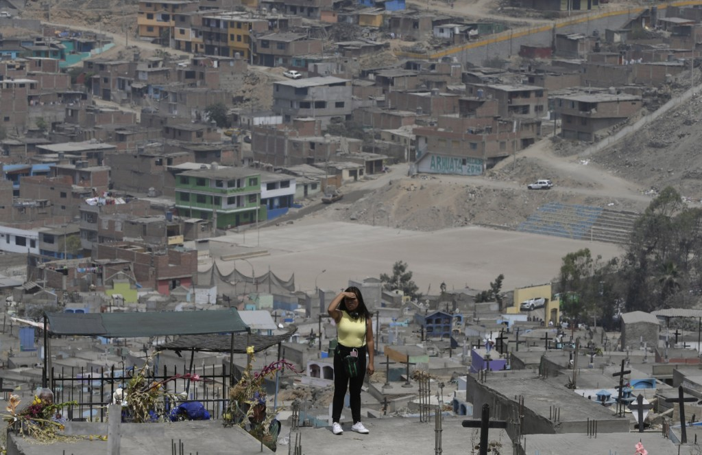 A relative watches Peruvian authorities demolish a Shining Path mausoleum in a cemetery on the outskirts of Lima, Peru, Saturday, Dec. 29, 2018. Peruv...