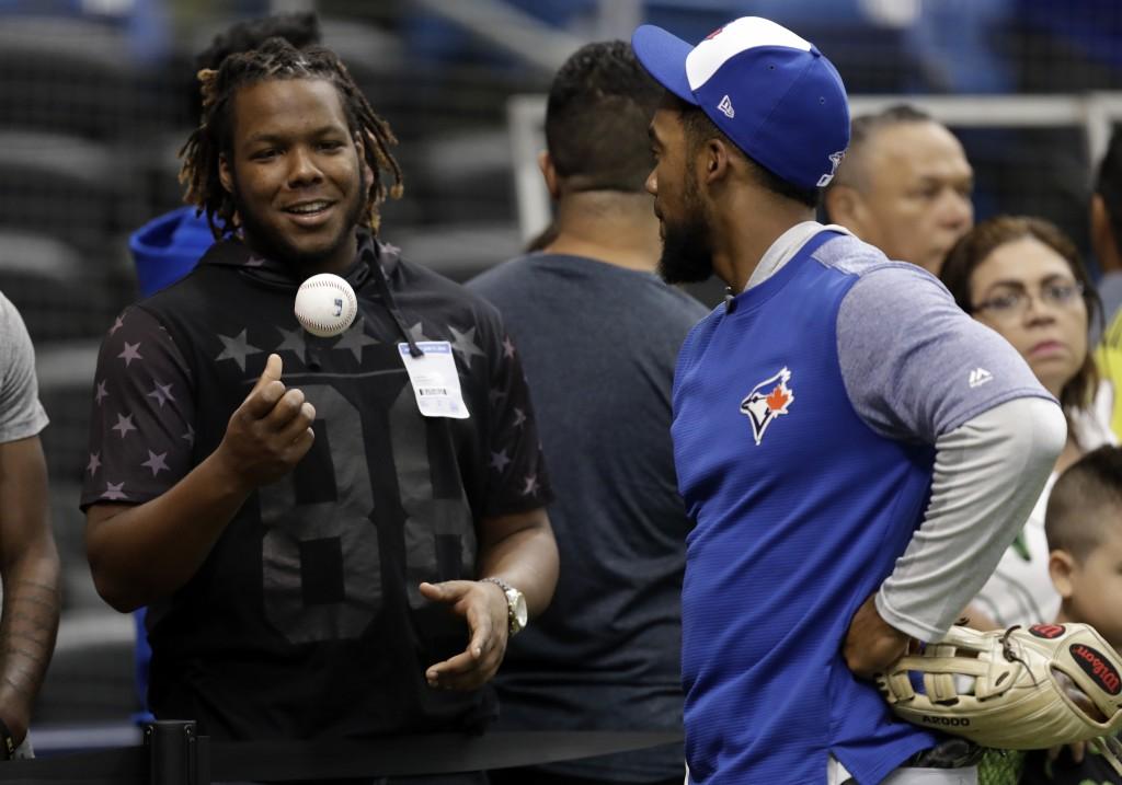 File-This June 11, 2018, file photo shows Toronto Blue Jays prospect Vlad Guerrero Jr., left, talking to right fielder Teoscar Hernandez before a base...