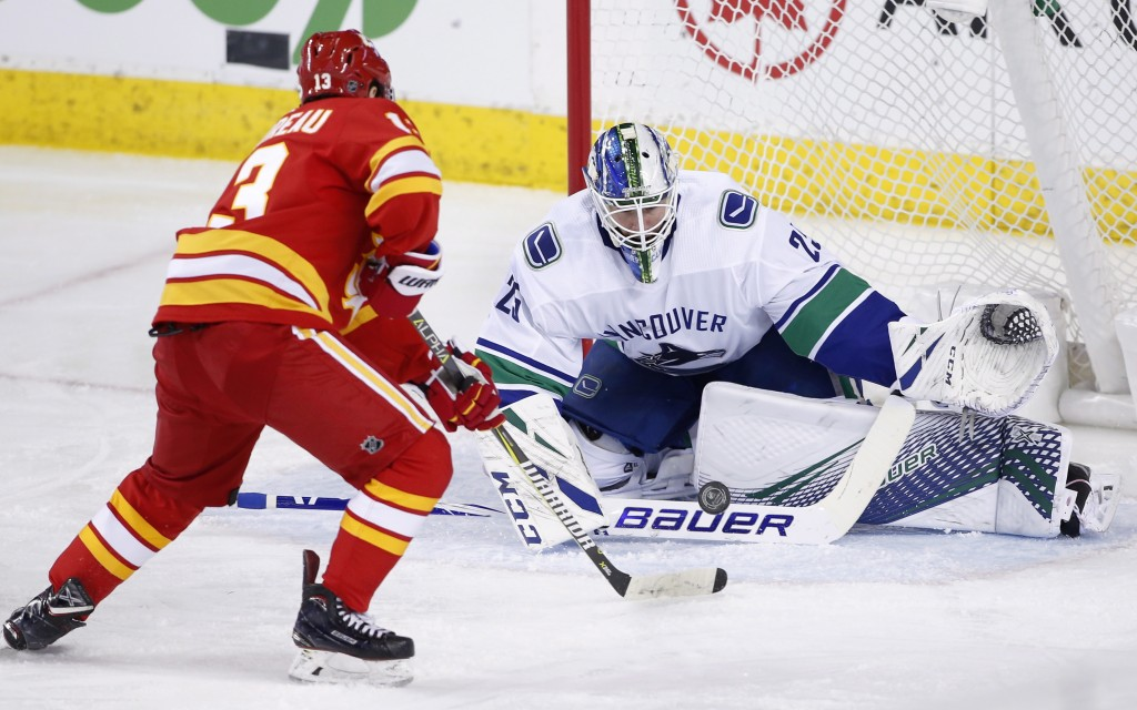Vancouver Canucks goalie Jacob Markstrom, from Sweden, makes a save against Calgary Flames' Johnny Gaudreau during the second period of an NHL hockey ...