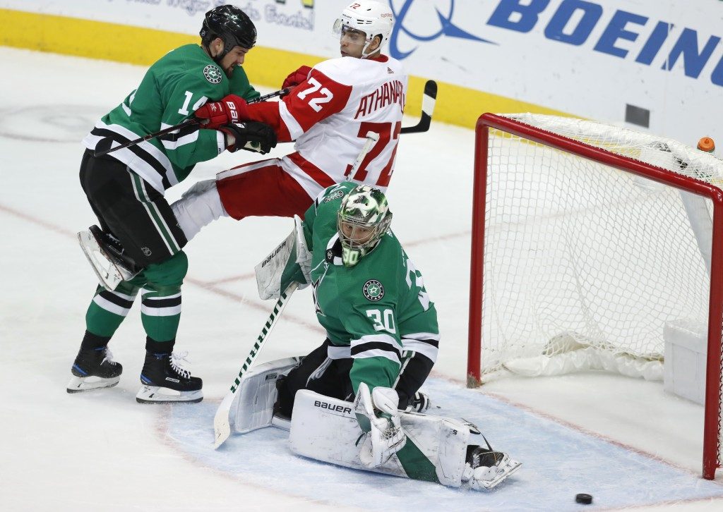 Detroit Red Wings center Andreas Athanasiou (72) is tied up by Dallas Stars left wing Jamie Benn (14) as goaltender Ben Bishop (30) reaches for a shot...