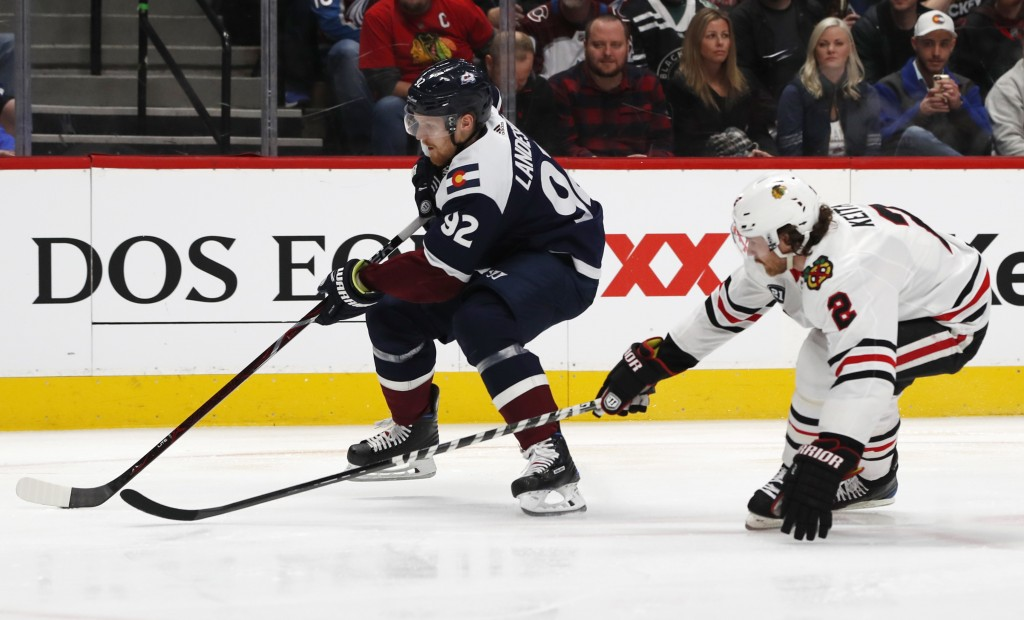 Colorado Avalanche left wing Gabriel Landeskog, left, drives past Chicago Blackhawks defenseman Duncan Keith to put a shot on the net in the first per...