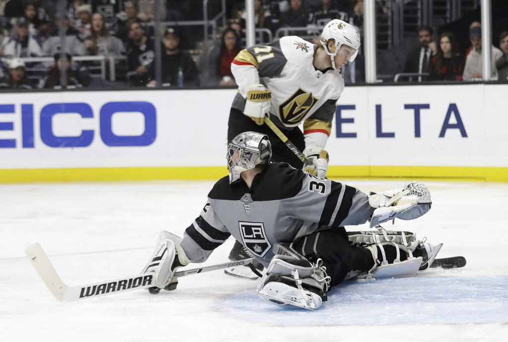 Vegas Golden Knights' William Karlsson, top, scores past Los Angeles Kings goaltender Jonathan Quick during the third period of an NHL hockey game Sat...