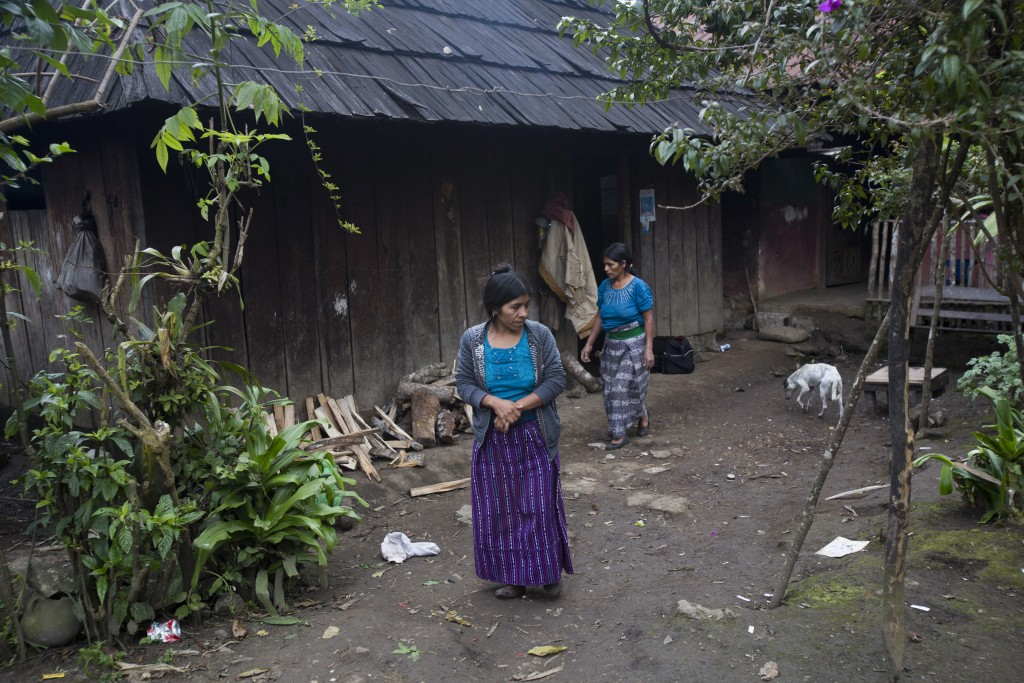 Catarina Alonzo Perez, mother of Felipe Gomez Alonzo, and her sister-in-law Maria, step outside their home in Yalambojoch, Guatemala, Saturday, Dec. 2...