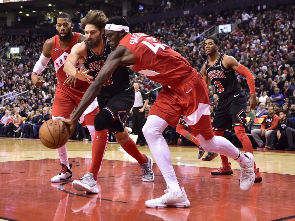 Toronto Raptors forward Pascal Siakam (43) collects a rebound in front of Chicago Bulls center Robin Lopez (42) during second-half NBA basketball game...