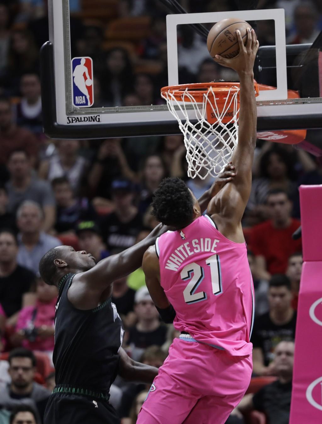 Miami Heat center Hassan Whiteside (21) shoots over Minnesota Timberwolves center Gorgui Dieng during the first half of an NBA basketball game, Sunday...