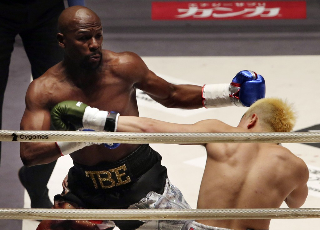 Floyd Mayweather Jr., left, exchanges a punch with Japanese kickboxer Tenshin Nasukawa, during their three-round exhibition match on New Year's Eve, a
