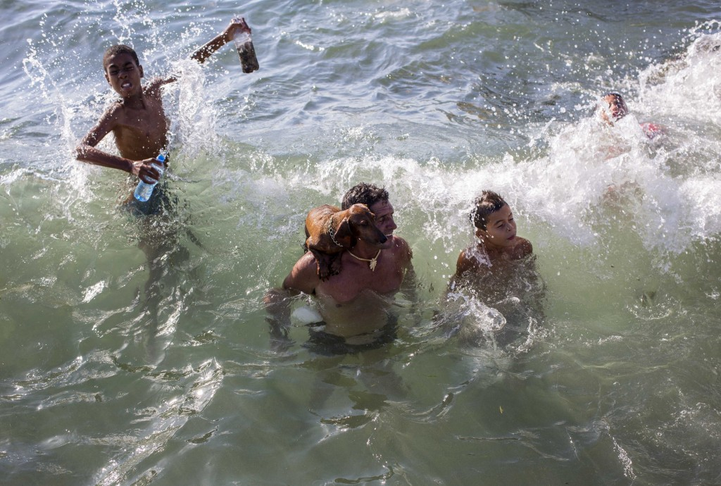 FILE - In this July 22, 2018 file photo, a man's pet dog stands on his shoulder as they take a dip in the ocean with other swimmers near Playita 16 in...