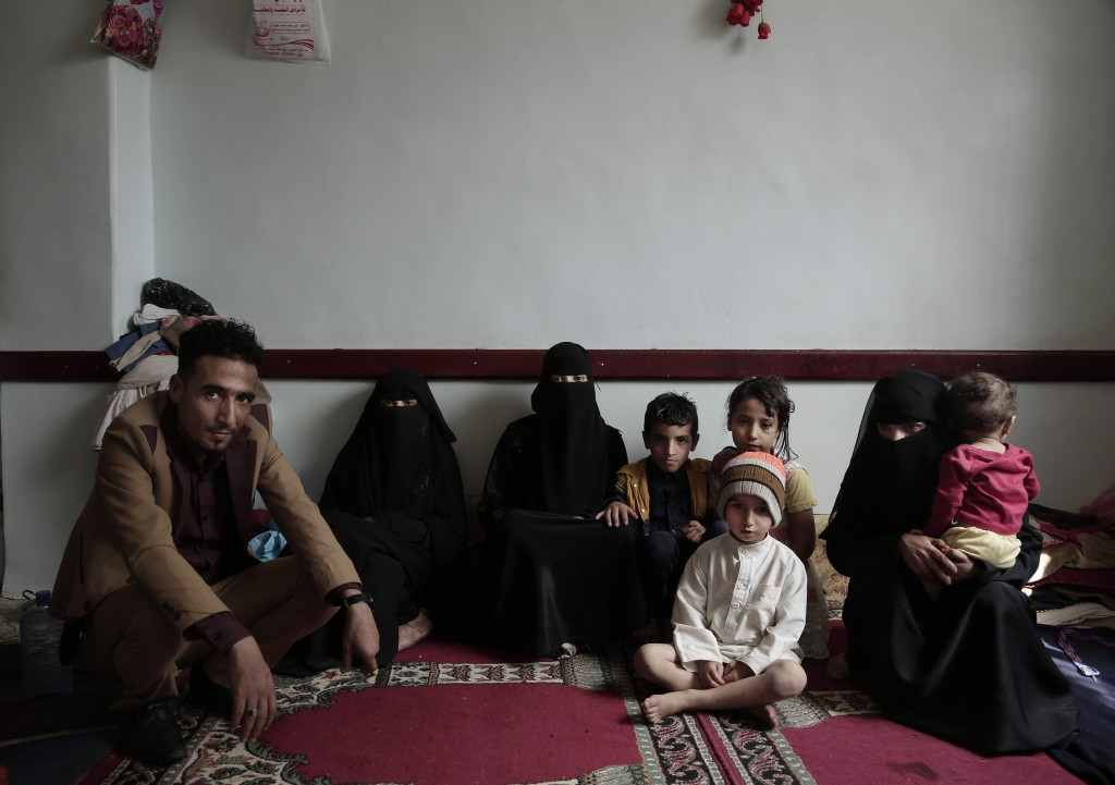 A family poses for a photograph in their room at a shelter for displaced persons in Ibb, Yemen, in this Aug. 3, 2018, photo. Across Yemen, factions an...