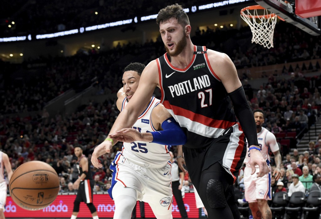 Portland Trail Blazers center Jusuf Nurkic, right, and Philadelphia 76ers guard Ben Simmons, left, go after a ball during the second half of an NBA ba...