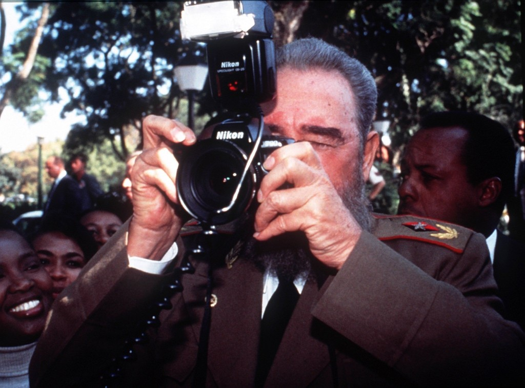 FILE - In this May 10, 1994 file photo, Cuban leader Fidel Castro briefly uses the camera of photojournalist Desmond Boylan outside the president's re...
