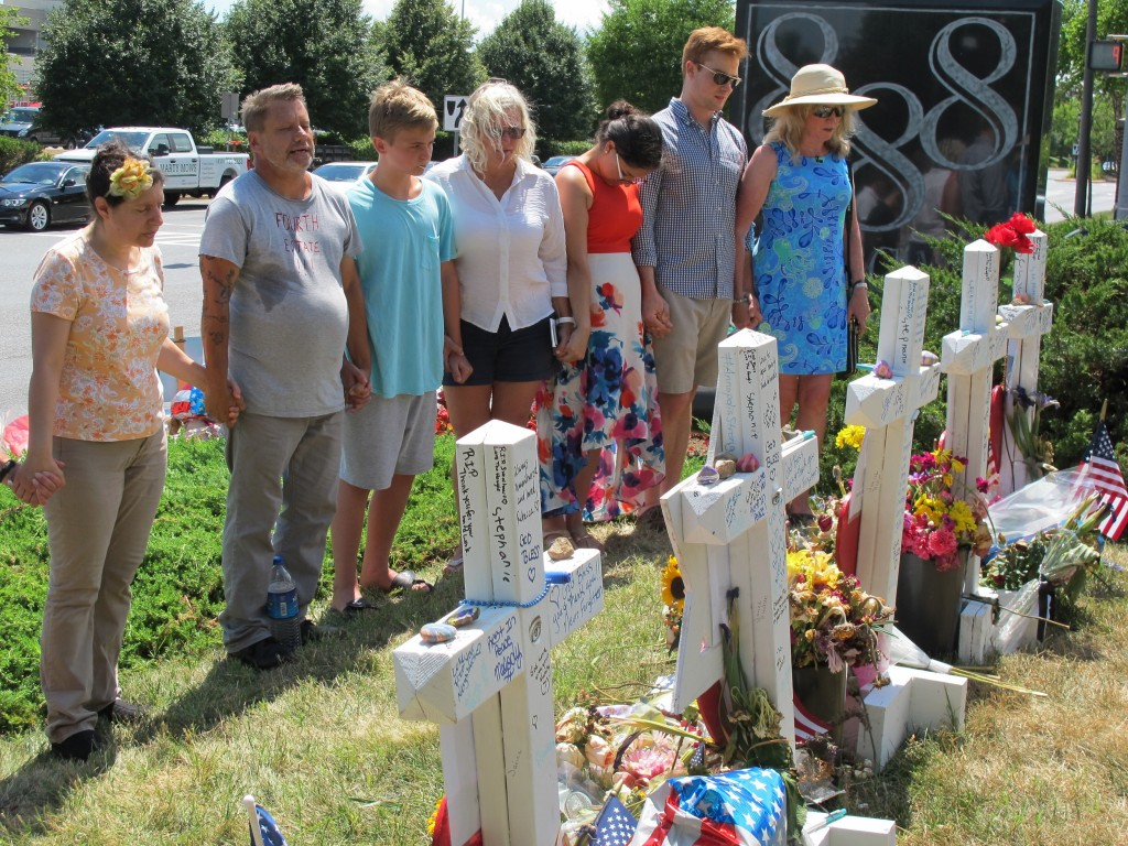 FILE - In this file photo dated Thursday, July 5, 2018, people pause for a moment of silence next to a memorial near the Capital Gazette building, in ...