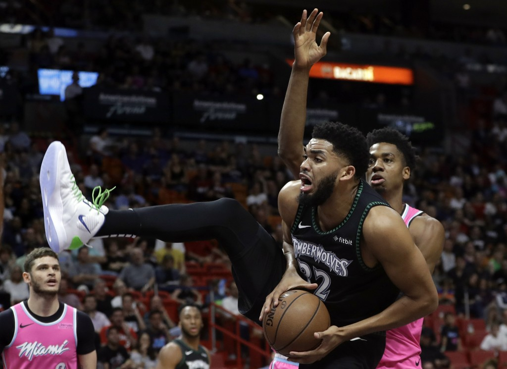 Minnesota Timberwolves center Karl-Anthony Towns (32) goes to the basket as Miami Heat center Hassan Whiteside, right, defends during the first half o...