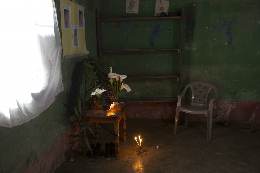 Calla lilies and candles adorn a makeshift altar honoring 8-year-old Felipe Gomez Alonzo, in his mother's home in Yalambojoch, Guatemala, Saturday, De...