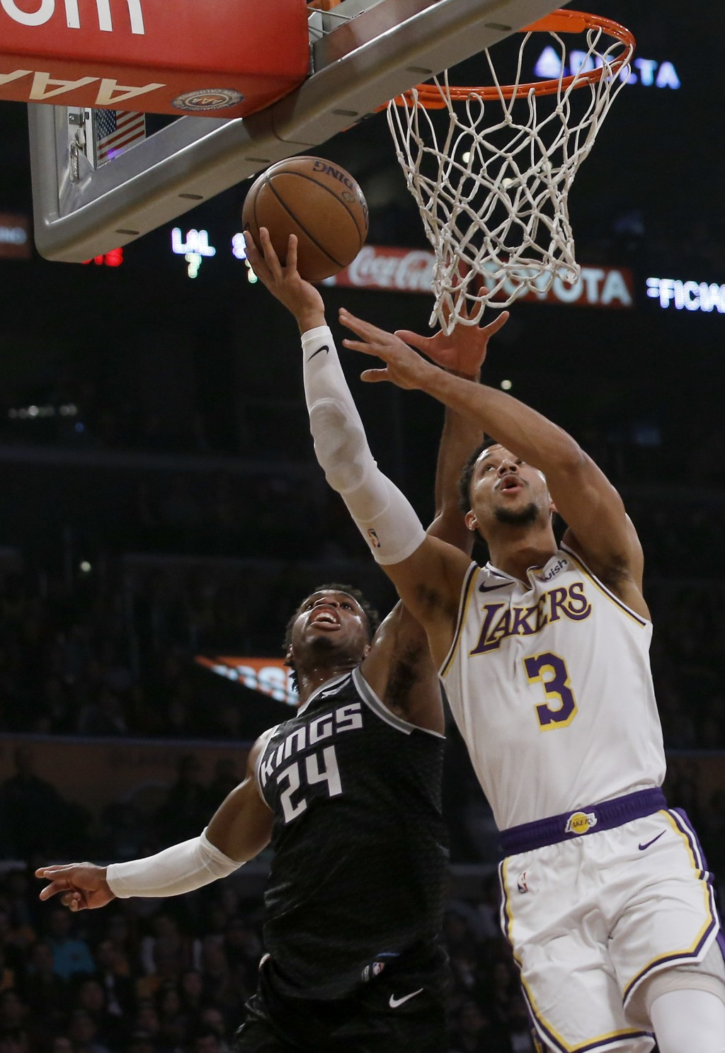 Los Angeles Lakers guard Josh Hart, right, shoots against Sacramento Kings guard Buddy Hield, left, during the first half of an NBA basketball game in...