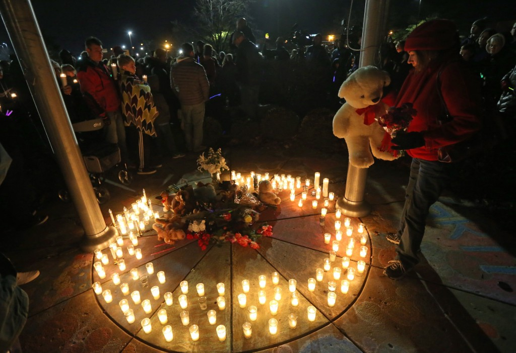Barb Moran places a stuffed animal in the center of a memorial in honor of Kate Kasten, her children, Zoe Kasten, 8, and Jonathan Kasten, 10, and Kate