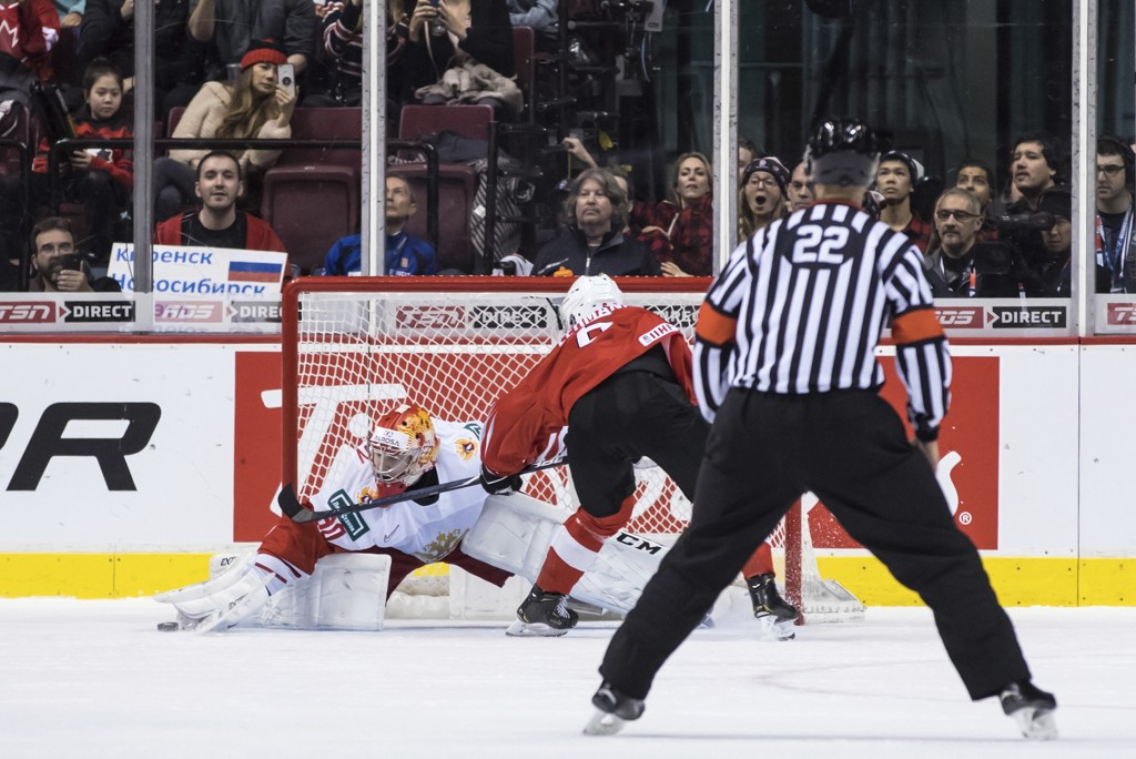 Russia goalie Danil Tarasov, back, stops Switzerland's Marco Lehmann on the first of two penalty shots awarded on the same play vie for the puck durin...