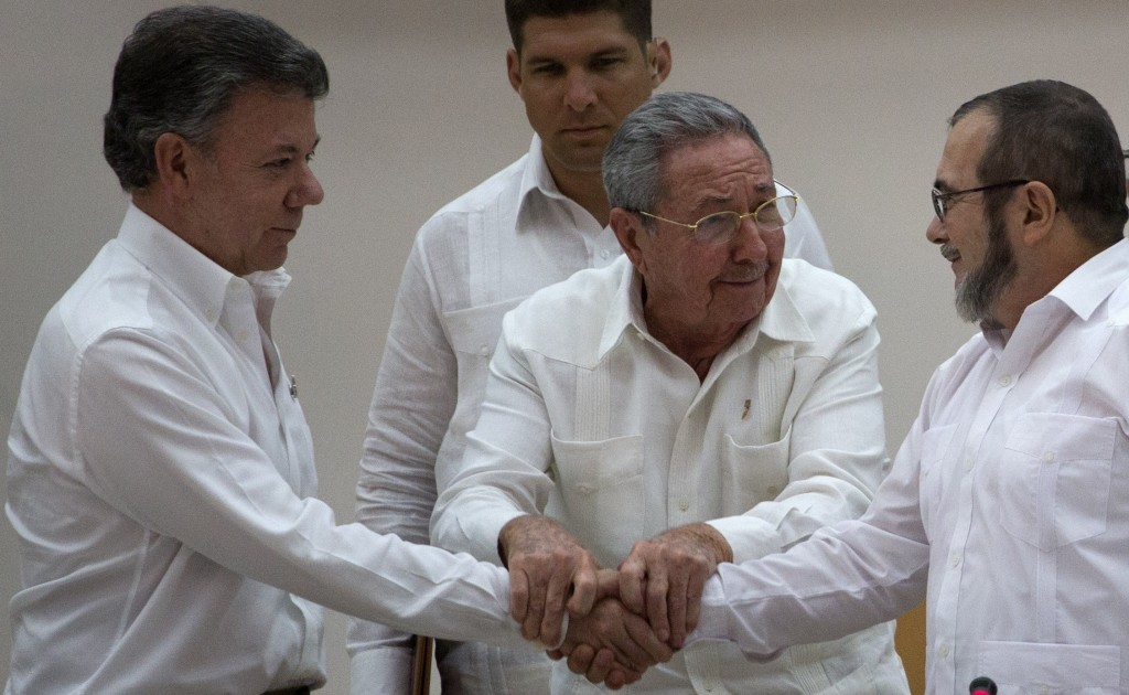FILE - In this Sept. 23, 2015 file photo, Cuba's President Raul Castro brings together the hands of Colombian President Juan Manuel Santos, left, and ...