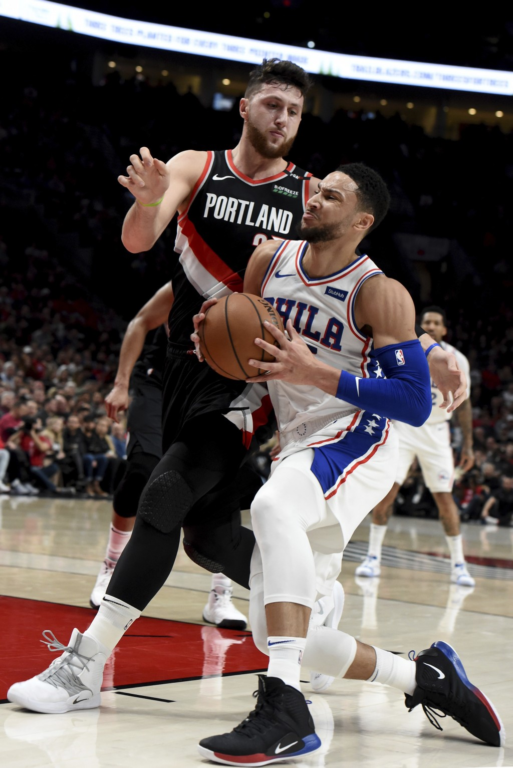 Philadelphia 76ers guard Ben Simmons, right, drives to the basket on Portland Trail Blazers center Jusuf Nurkic, left, during the first half of an NBA...