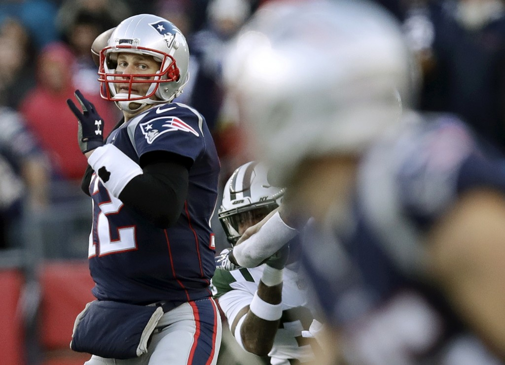 New England Patriots quarterback Tom Brady, left, drops back to pass to wide receiver Chris Hogan, foreground, during the second half of an NFL footba...