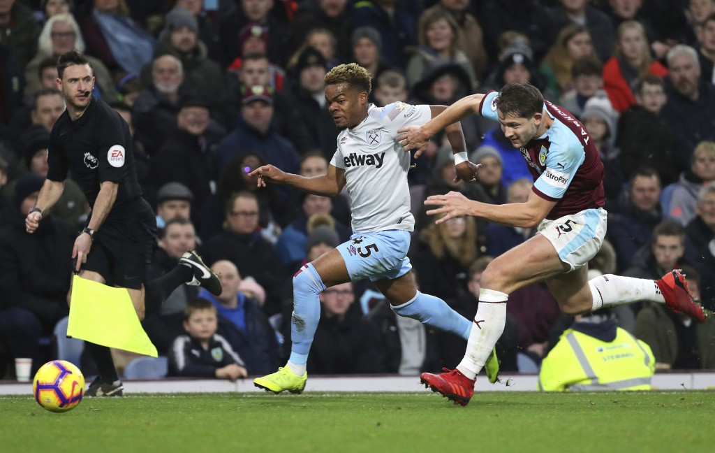 West Ham United's Grady Diangana and Burnley's James Tarkowski, right, during their English Premier League soccer match at Turf Moor in Burnley, Engla...