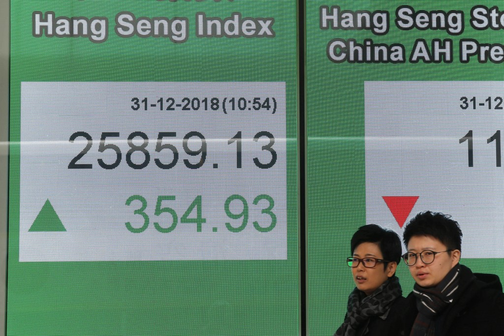 People walk past an electronic board displaying the Hong Kong share index outside a bank in Hong Kong, Monday, Dec. 31, 2018. Shares are mostly higher...