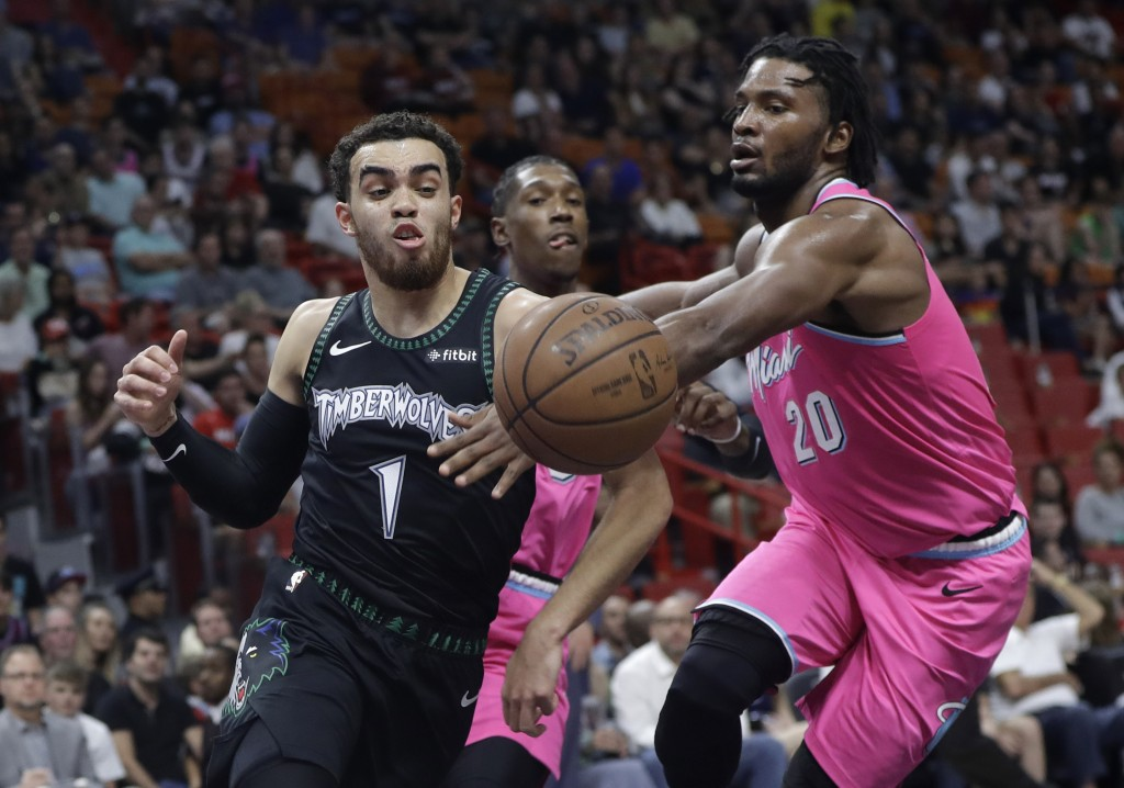 Miami Heat forward Justise Winslow (20) defends Minnesota Timberwolves guard Tyus Jones (1) during the first half of an NBA basketball game, Sunday, D...