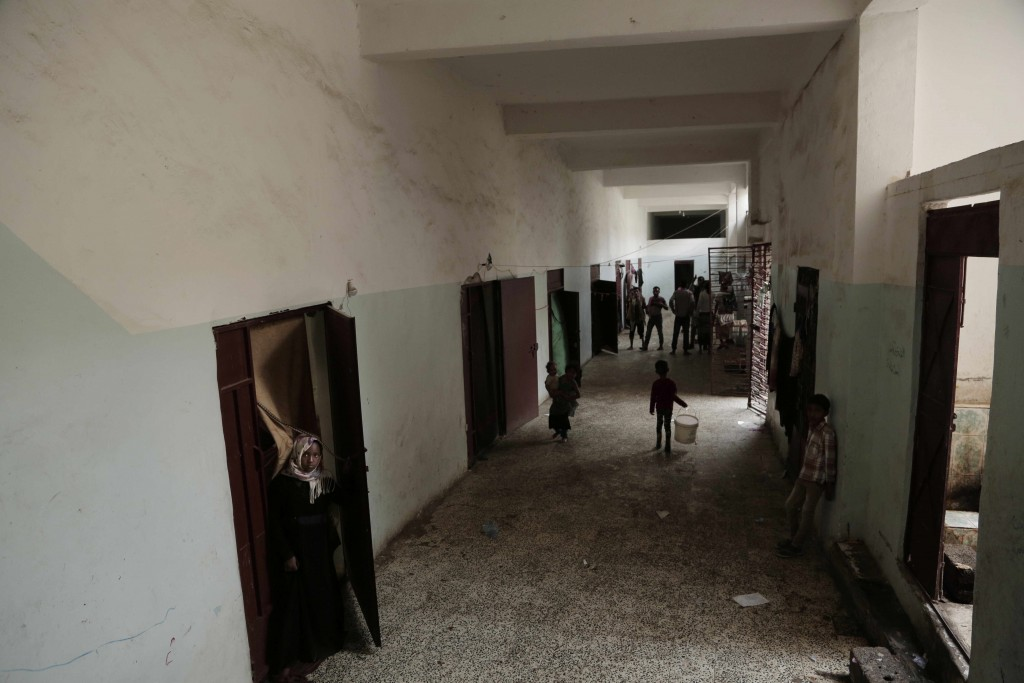 People stand near their rooms inside a shelter for displaced persons in Ibb, Yemen, in this Aug. 3, 2018, photo. Across Yemen, factions and militias o...
