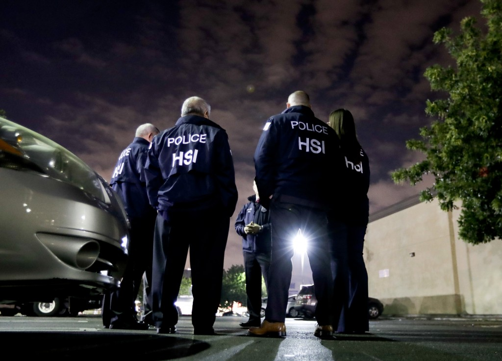 FILE - In this Jan. 10, 2018, file photo, U.S. Immigration and Customs Enforcement agents gather before serving an employment audit notice at a 7-Elev...