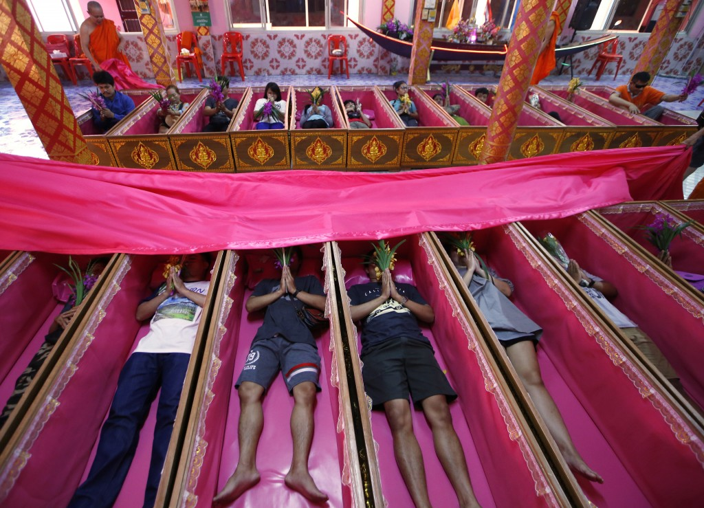 In this Monday, Dec. 31, 2018, file photo, worshippers pray as they take turns sitting in coffins at the Takien temple in suburban Bangkok, Thailand. ...