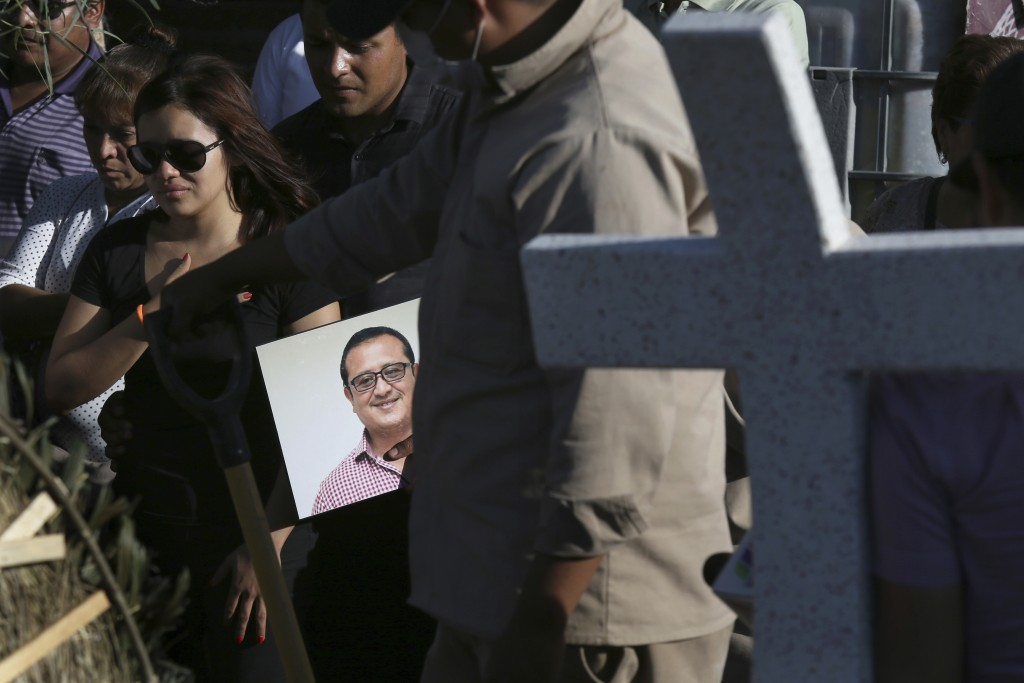FILE - In this file photo dated Thursday, May 31, 2018, a man carries a portrait of slain journalist Hector Gonzalez Antonio as his daughter, left, mo...