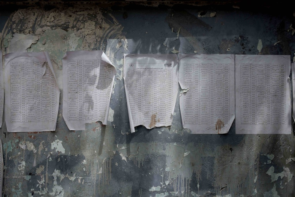 A worn-out list of registered names for aid by Relief International, part of the World Food Program, is posted in Aden, Yemen in this July 23, 2018 ph...