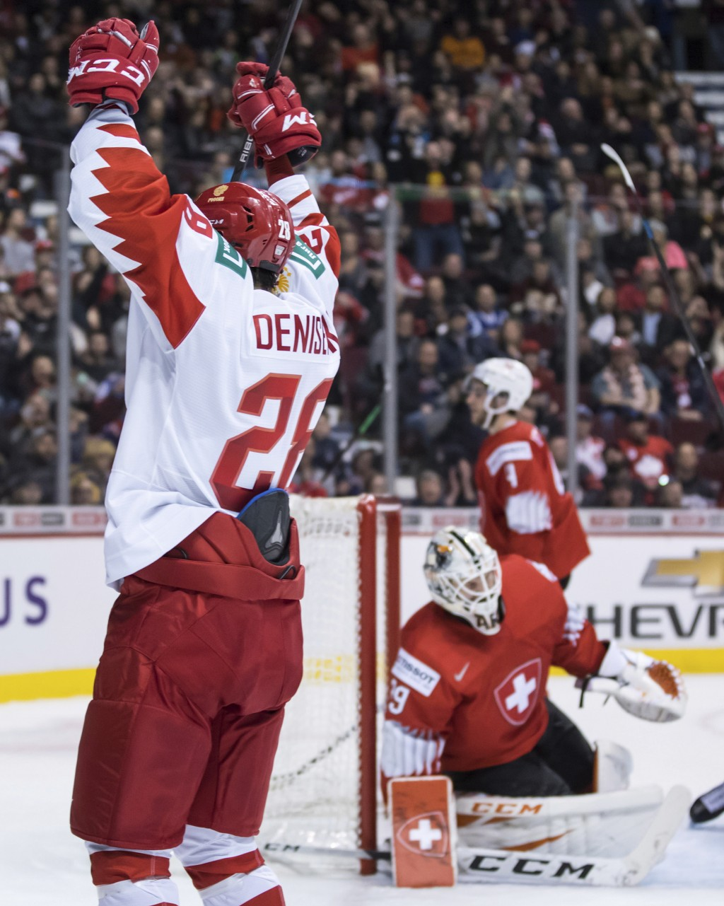 Russia's Grigori Denisenko, front left, celebrates his goal against Switzerland goalie Akira Schmid vie for the puck during the second period of a wor...