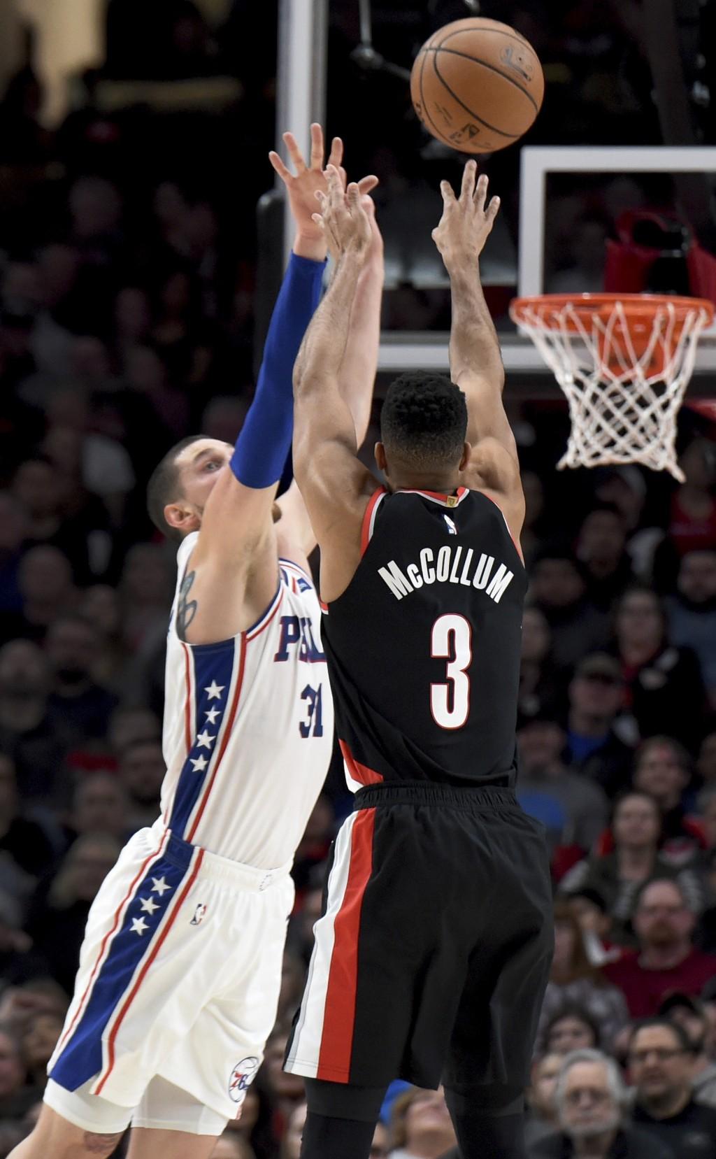 Portland Trail Blazers guard CJ McCollum, right, hits a shot over Philadelphia 76ers forward Mike Muscala, left, during the first half of an NBA baske...