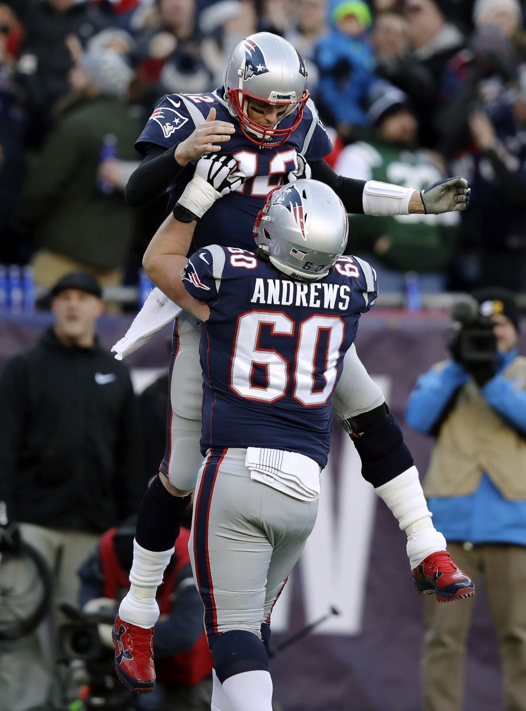 New England Patriots quarterback Tom Brady, top, gets a lift from center David Andrews as they celebrate Brady's touchdown pass to Phillip Dorsett dur...