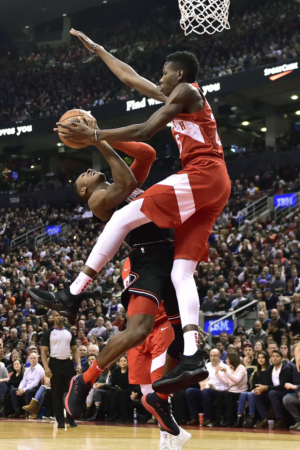 Toronto Raptors forward Chris Boucher (25) fouls Chicago Bulls guard Kris Dunn (32) driving to the net during the first half of an NBA basketball game...