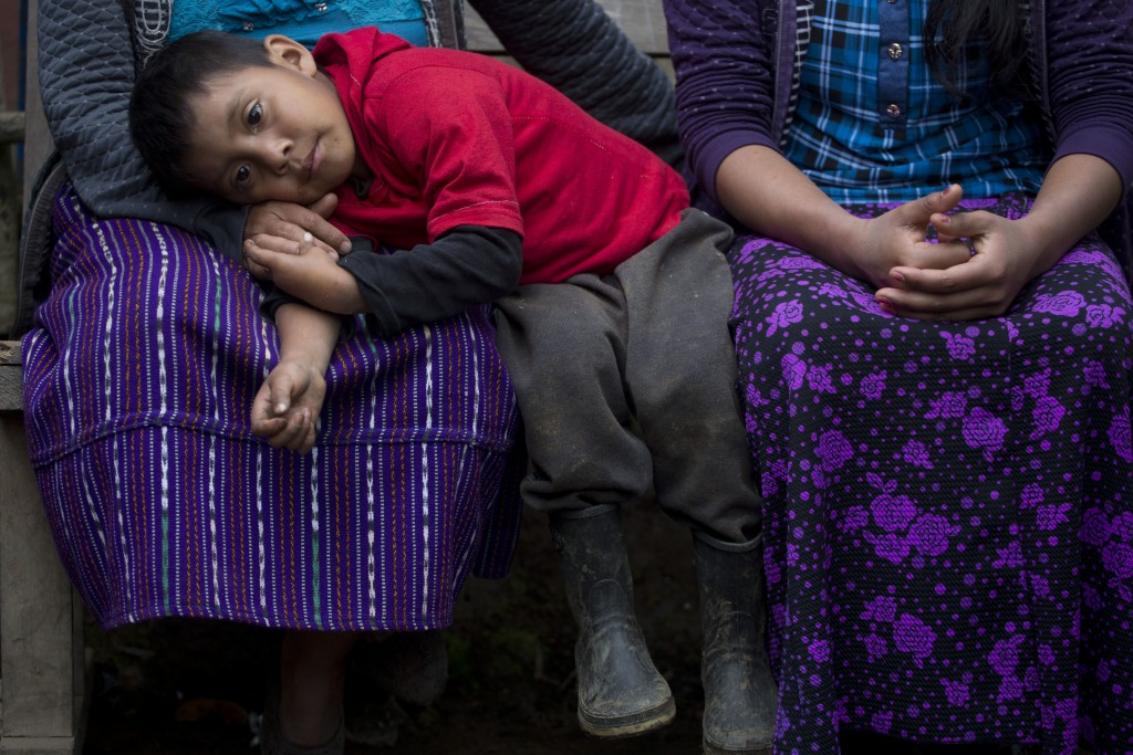 Six-year-old Mateo, the brother of Felipe Gomez Alonzo an 8-year-old Guatemalan boy who died in U.S. custody, rests his head on his mother's lap in th...
