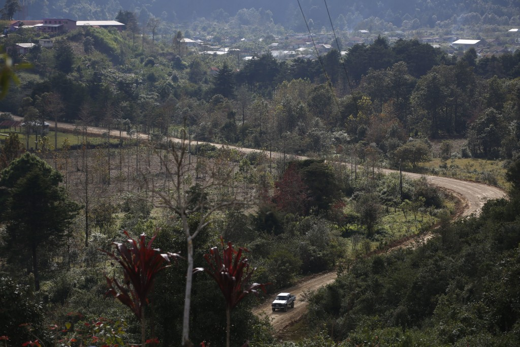 A truck drives past on a dirt road in Yalambojoch, Guatemala, Saturday, Dec. 29, 2018. There are no jobs in Yalambojoch, and people live off local com...