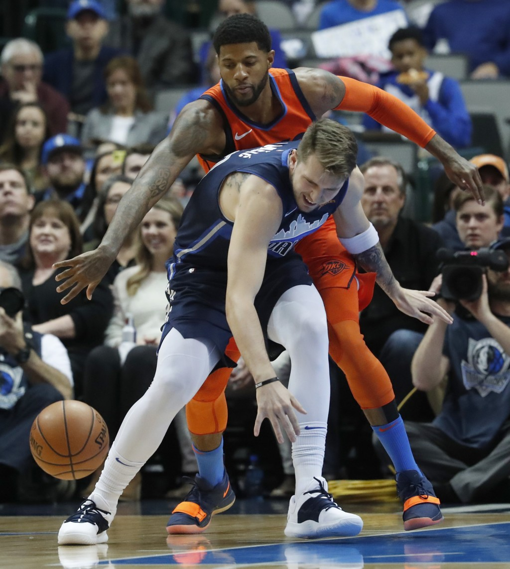 Oklahoma City Thunder forward Paul George, top, reaches to disrupt the dribble by Dallas Mavericks forward Luka Doncic, of Germany, during the first h...