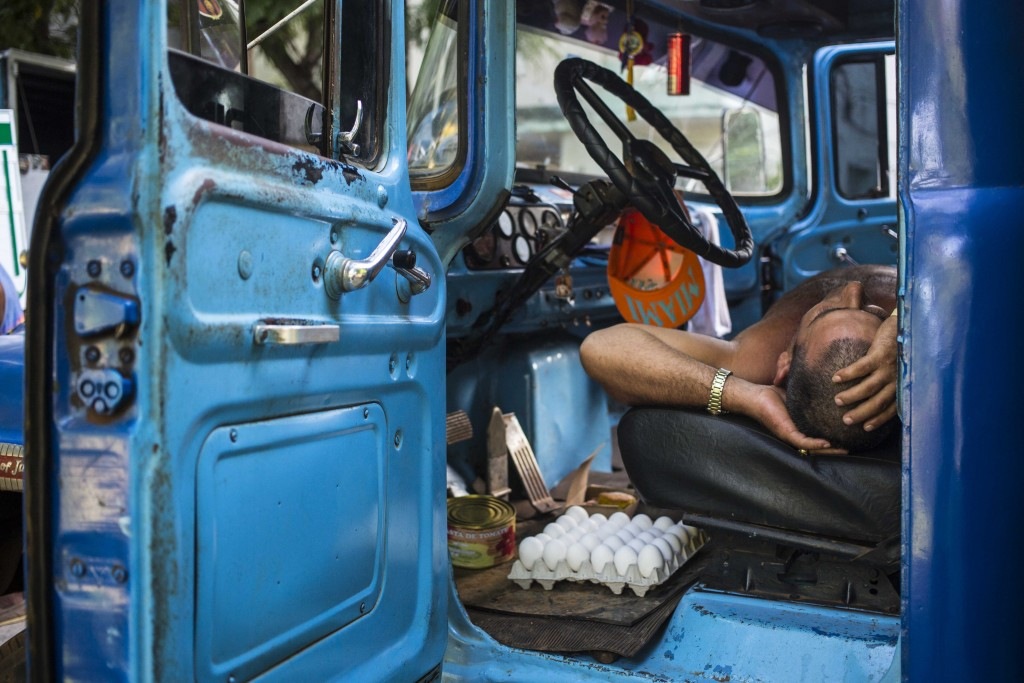 FILE - In this July 21, 2018 file photo, a driver takes a nap in the cabin of his truck at an outdoor food market in Havana, Cuba. (AP Photo/Desmond B...